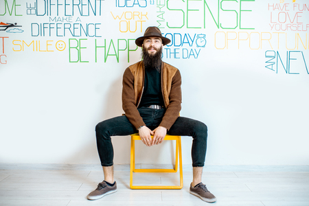 Full body portrait of a stylish bearded man on the wall background with various inscriptions on the topic of mental health indoors