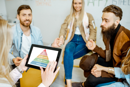 People holding digital tablet with mental pyramid sheme during the psychological therapy, close-up
