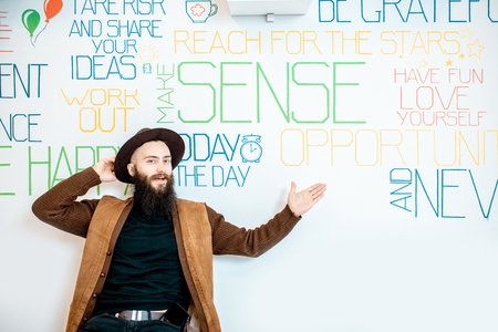 Portrait of a stylish bearded man on the wall background with various inscriptions on the topic of mental health indoors Reklamní fotografie