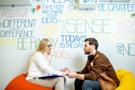 Man with senior female psychologist or mental coach sitting together during the psychological counseling on the wall background with various inscriptions on the topic of mental health indoors.