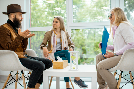 Young couple having misunderstandings during the psychological counseling with senior female psychologist in the office