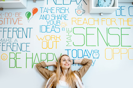 Portrait of a young smiling woman on the wall background with various inscriptions on the topic of mental health indoors