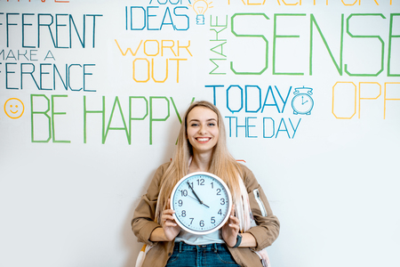 Portrait of a young smiling woman holding clock on the wall background with various inscriptions on the topic of mental health indoors Reklamní fotografie