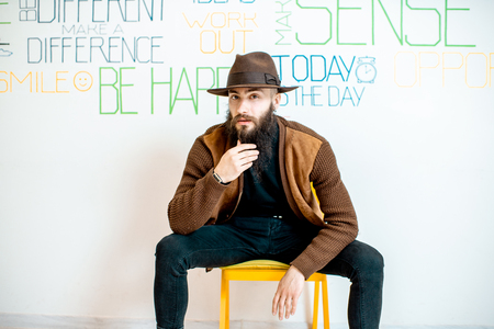 Portrait of a stylish bearded man on the wall background with various inscriptions on the topic of mental health indoors Фото со стока
