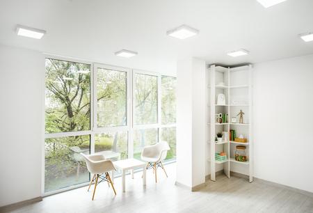 Vista interior de la espaciosa oficina blanca con ventana grande, libros y lugar de trabajo del terapeuta de psicología