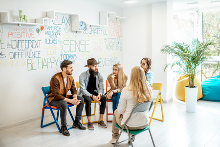 Group of young people sitting together during the psychological therapy with psychologist solving some mental problems in the office