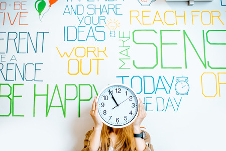 Portrait of a young smiling woman holding clock on the wall background with various inscriptions on the topic of mental health indoors Banque d'images