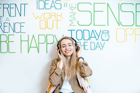 Portrait of a young smiling woman with headphones on the wall background with various inscriptions on the topic of mental health Reklamní fotografie - 122966454