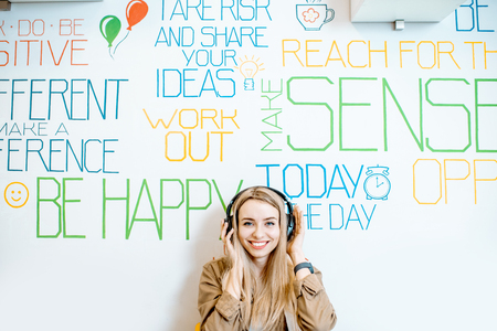 Portrait of a young smiling woman with headphones on the wall background with various inscriptions on the topic of mental health