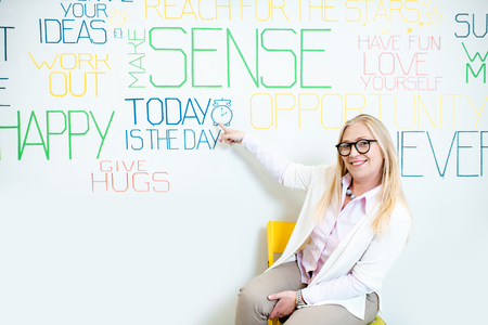 Portrait of a senior woman as a mental coach on the wall background with various inscriptions on the topic of mental health indoors