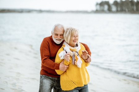 Lovely senior couple dressed in colorful sweaters hugging on the sandy beach, enjoying free time during retirement near the sea