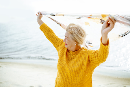Senior woman in bright sweater enjoying sea breeze, holding scarf above the head on the sandy beach