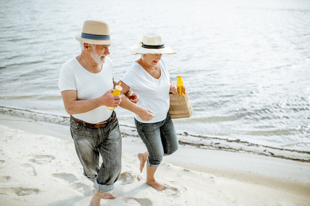 Happy senior couple dressed in white t-shirts and hats walking together on the sandy beach during their retirement Reklamní fotografie