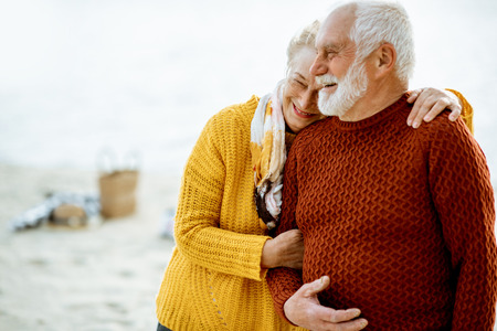 Portrait of a happy senior couple dressed in colorful sweaters hugging on the sandy beach, enjoying free time during retirement near the sea
