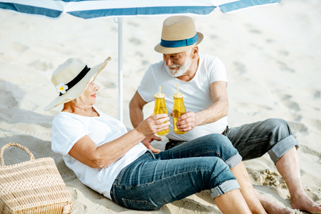 Happy senior couple relaxing, lying with drinks on the sandy beach, enjoying their retirement near the sea Reklamní fotografie