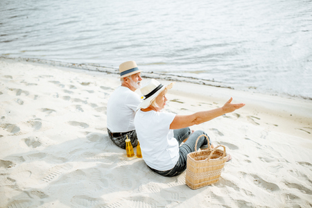 Senior couple sitting together with drinks and bag on the sandy beach, enjoying their retirement near the sea, rear view 版權商用圖片