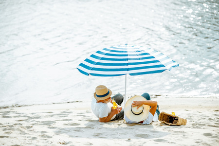 Senior couple sitting together under umbrella on the sandy beach, enjoying their retirement near the sea, rear view