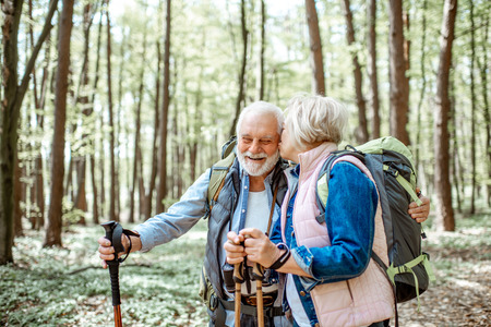 Beautiful senior couple hiking with backpacks and trekking sticks in the forest. Concept of active lifestyle on retirement 免版税图像