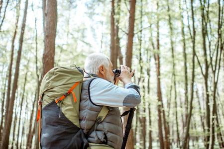 Senior man kijkt met een verrekijker tijdens het reizen met rugzak in het bos Stockfoto