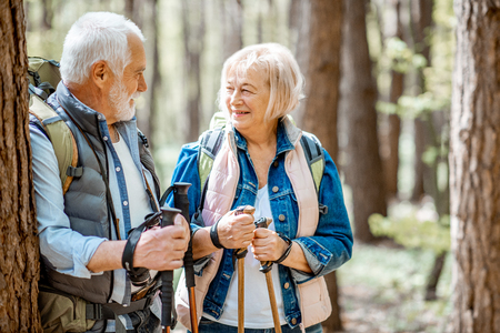 Senior couple resting near the tree while traveling with backpacks and trekking sticks in the forest. Concept of an active lifestyle on retirement