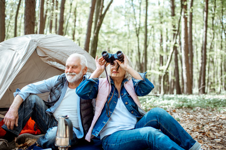 Senior couple sitting together at the campsite with tent and backpacks, enjoying nature with binoculars in the forest Фото со стока