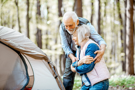 Senior couple hugging during the picnic at the campsite in the forest Stock Photo