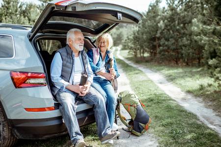 Senior koppel zit aan de kofferbak, genietend van de natuur tijdens het reizen in het jonge dennenbos