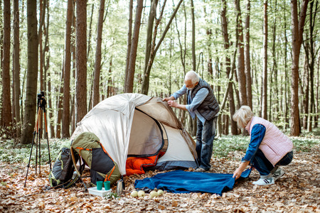 Senior couple preparing for rest, laying out a tent and plaid in the forest Stock Photo