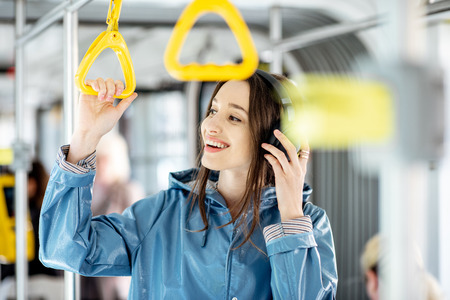 Young stylish woman enjoying trip in the public transport, standing with headphone while moving in the modern tram Foto de archivo