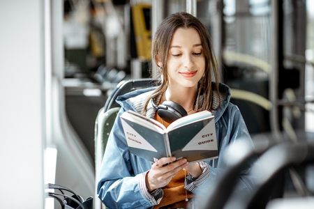 Young woman reading book while moving in the modern tram, happy passenger at the public transport Фото со стока