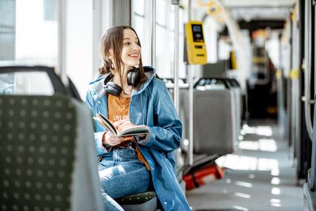 Libro de lectura de mujer joven mientras se mueve en el tranvía moderno, pasajero feliz en el transporte público