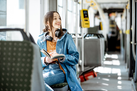Young woman reading book while moving in the modern tram, happy passenger at the public transport Banque d'images