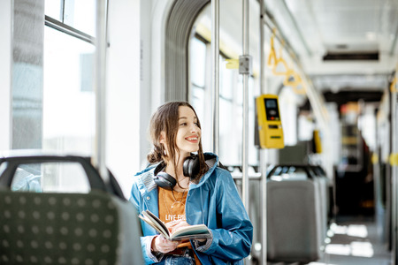 Young woman reading book while moving in the modern tram, happy passenger at the public transport Zdjęcie Seryjne - 122705561