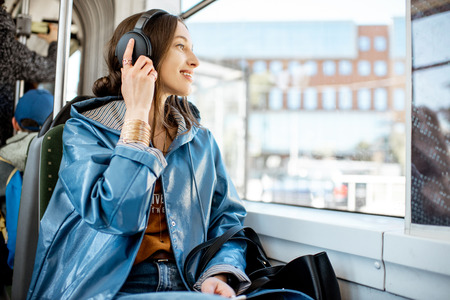 Young woman passenger enjoying trip at the public transport, sitting with headphones near the window in the modern tram