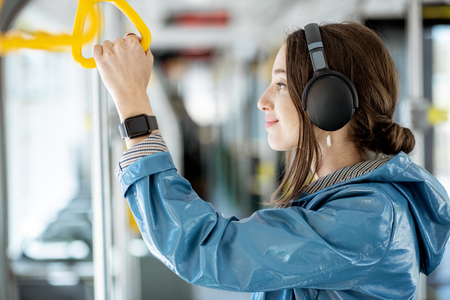 Young woman holding handle while moving in the modern tram. Happy passenger enjoying trip at the public transport