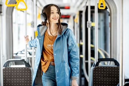 Young stylish woman with headphones while moving in the modern tram. Happy passenger enjoying trip at the public transport Фото со стока