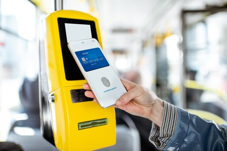 Pagar sin contacto con el teléfono inteligente para el transporte público en el tranvía, vista de cerca Foto de archivo
