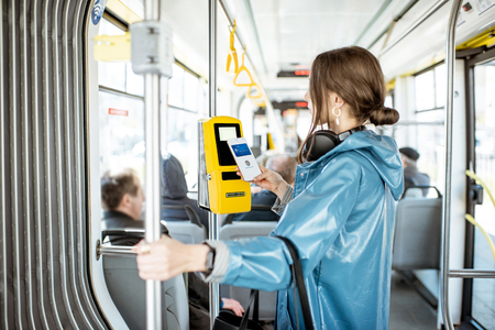 Woman paying conctactless with smartphone for the public transport in the tram