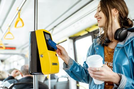 Frau zahlt kontaktlos mit Bankkarte für die öffentlichen Verkehrsmittel in der Straßenbahn Standard-Bild