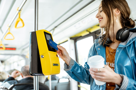 Vrouw die contactloos betaalt met bankkaart voor het openbaar vervoer in de tram Stockfoto