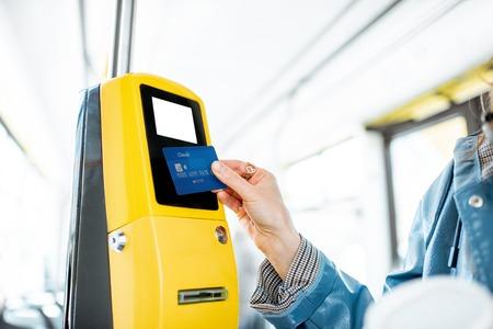 Donna che paga senza contatto con carta di credito per il trasporto pubblico in tram Archivio Fotografico