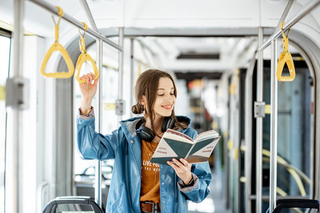Young woman reading book while standing in the modern tram, happy passenger moving by comfortable public transport Imagens