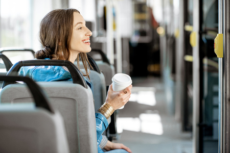 Portrait of a young woman passenger enjoying trip at the public transport, sitting with coffee in the modern tram, back view