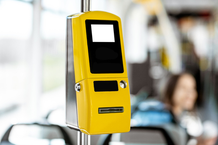 Yellow ticket machine in the modern tram with female passenger on the background