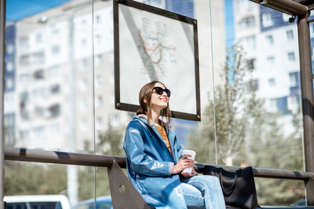 Young stylish woman waiting for the public transport while sitting at the modern tram station outdoors