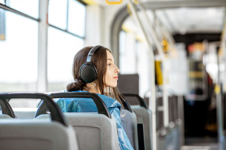 Young woman passenger enjoying trip at the public transport, sitting with headphones in the modern tram. Back view