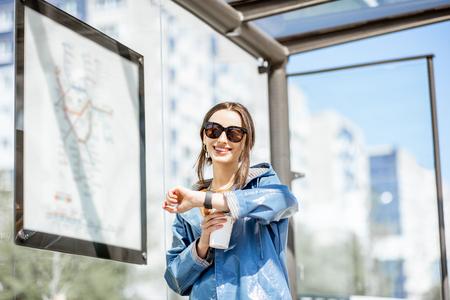 Junge Frau, die die Zeit überprüft, während sie draußen an der Straßenbahnhaltestelle steht