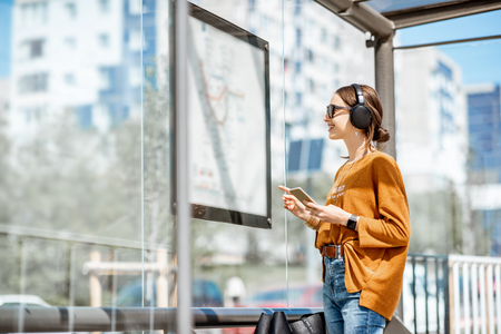 Woman looking on the scheme of public transport while standing at the tram station outdoors