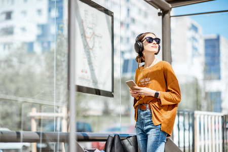 Young stylish woman waiting for the public transport while standing at the modern tram station outdoors Stock Photo