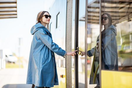 Woman entering the door of the modern tram at the station Banco de Imagens